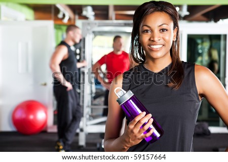 A shot of a happy black female athlete holding a water bottle in a gym