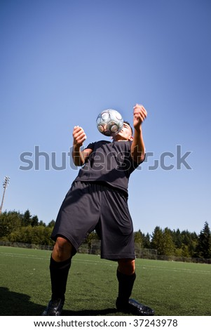 A shot of a hispanic soccer or football player controlling the ball with his chest - stock photo