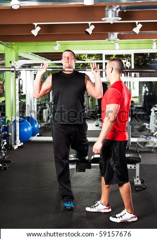 A shot of a male personal trainer assisting a male athlete training - stock photo