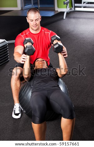 A shot of a male personal trainer assisting a woman lifting weights - stock photo