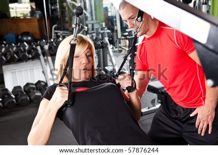 A shot of a male personal trainer assisting a woman pulling weights - stock photo