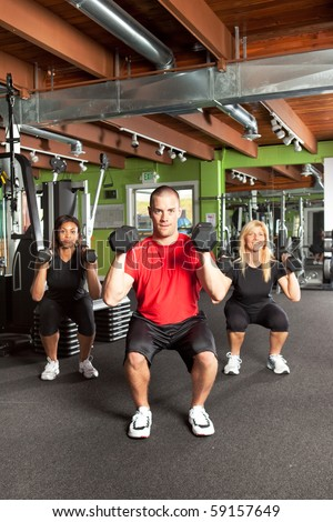 A shot of a male personal trainer training with two female athletes in the gym - stock photo