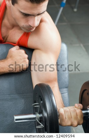 A shot of a male weightlifter doing a bicep curl with a barbell. - stock photo