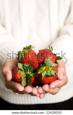 A shot of a man holding a bunch of strawberries