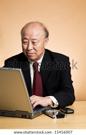 A shot of a mature asian businessman working on his laptop - stock photo