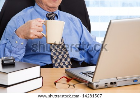A shot of a mature businessman holding a coffee cup working on his laptop in the office