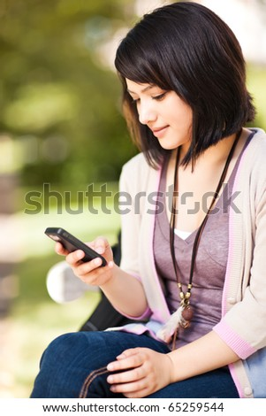 A shot of a mixed race girl texting on the phone at campus - stock photo