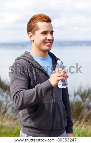 A shot of a mixed race man holding water bottle outdoor - stock photo