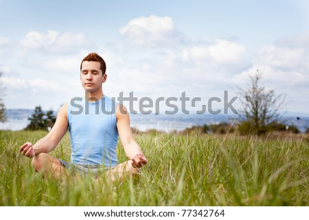 A shot of a mixed race man practicing yoga outdoor - stock photo