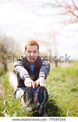 A shot of a mixed race man stretching outdoor - stock photo