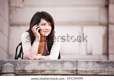 A shot of a mixed race student talking on the phone - stock photo