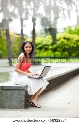 A shot of a mixed race woman talking on the phone and working on her laptop - stock photo