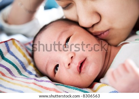A shot of a mother affectionately kissing her baby boy - stock photo