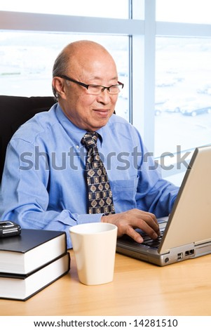 A shot of a senior asian businessman working on his laptop at the office - stock photo