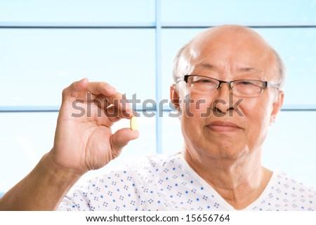 A shot of a senior asian man holding a pill - stock photo