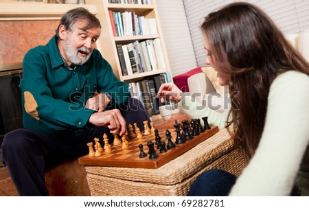 A shot of a senior caucasian male playing chess with his granddaughter - stock photo