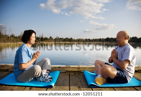 A shot of a senior couple practicing a yoga exercise and meditating outdoor - stock photo