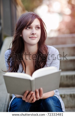 A shot of a smiling college student reading a book - stock photo