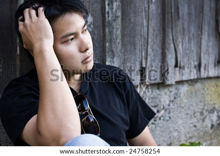 A shot of a stressed asian male outdoor - stock photo