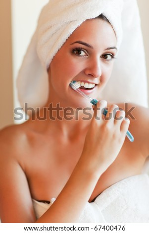 A shot of a young beautiful woman brushing her teeth