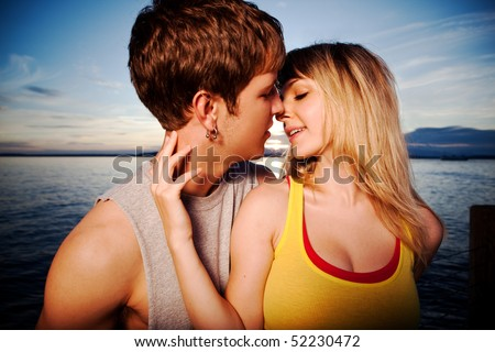 A shot of a young caucasian couple kissing outdoor - stock photo