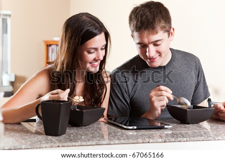 A shot of a young couple eating breakfast and reading on tablet PC