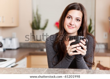 A shot of a young woman holding a cup of coffee - stock photo