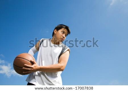 A shot of an asian basketball player holding a basketball - stock photo