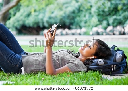 A shot of an Asian college student listening to music lying down on the grass on campus - stock photo