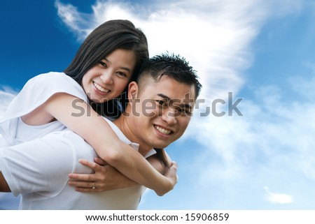 A shot of an asian couple outdoor doing a piggback ride - stock photo