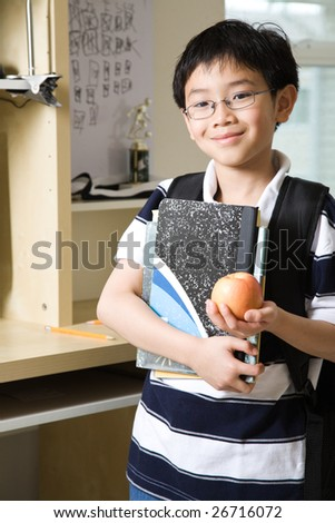 A shot of an asian kid studying at home holding an apple