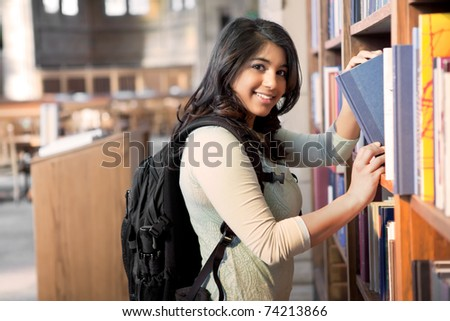 A shot of an asian student getting books in a library - stock photo
