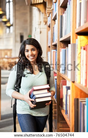 A shot of an asian student holding books at the library - stock photo