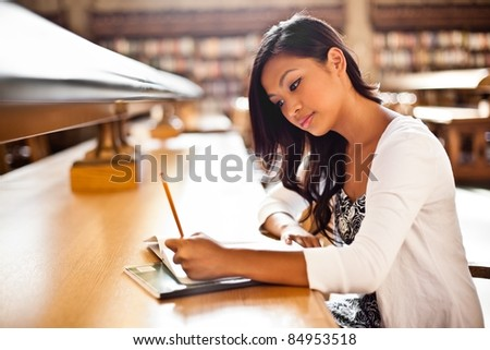 A shot of an Asian student studying in the library