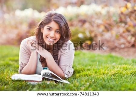 A shot of an asian student studying on campus lawn - stock photo