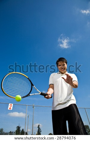A shot of an asian tennis player hitting a tennis ball - stock photo