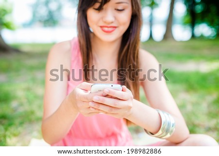 A shot of an Asian texting on the phone - stock photo