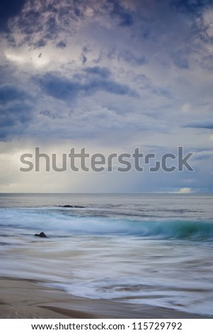 A shot of an early morning storm coming into Corona Beach in Newport Beach California with the surf crashing into rocks. - stock photo