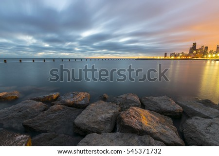 A shot of an empty lake taken from a pier during the sunrise with Chicago's Skyline visible in the background. Beautiful rocks are present in the foreground.