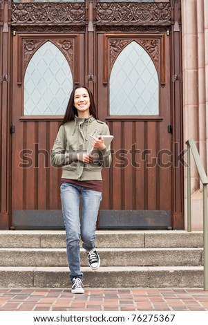 A shot of an ethnic college student carrying a book on campus - stock photo