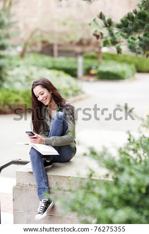 A shot of an ethnic college student texting on the phone at campus - stock photo