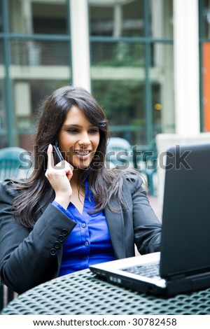 A shot of an indian businesswoman talking on the phone and working on her laptop outdoor - stock photo