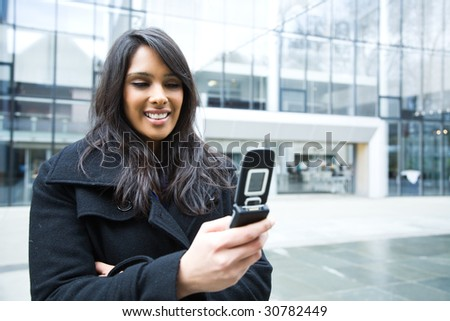 A shot of an indian businesswoman texting on the phone  outdoor - stock photo