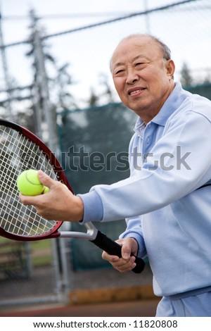 A shot of an senior asian man playing tennis - stock photo