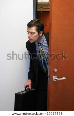 A shot of businessman peaking his head out of a door to see if he can sneak out the office. - stock photo