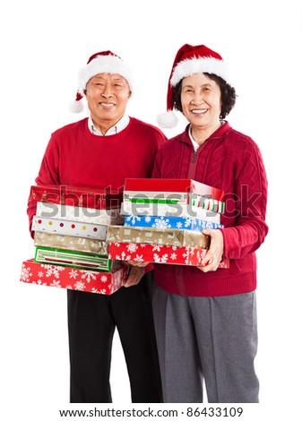 A shot of senior Asian couple carrying Christmas presents celebrating Christmas - stock photo