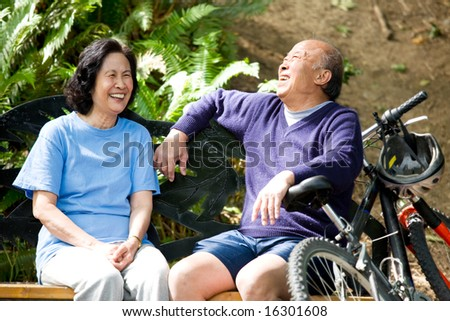A shot of senior asian couple sitting on a bench at a park - stock photo
