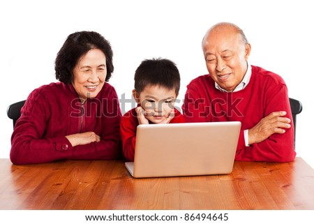 A shot of senior Asian grandparents using computer with their grandson