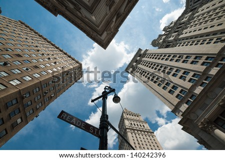 A shot taken from a street corner, pointing high to sky, showing the top of the tall skyscrapers of New York City. A sensation of vertigo. - stock photo