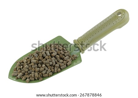 A shovel full of compressed Organic Animal-based Fertilizer Pellets isolated on white - stock photo